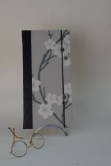 <h5>Carnet de Poète</h5><p>Carnet cousu, cuir noir et papier décor fleurs du japon. élastique de fermeture et petite déco boutons fleurs coordonné à l'ensemble.</p>