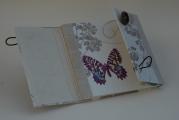 <h5>Livre d'Or double rabat</h5><p>Pour une dame en retraite amoureuse des papillons  !  Toile enduite et toile de lin ouvert sur 2 rabats boutons bois.</p>